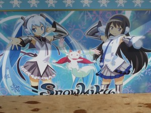 グッズ販売ブースの壁に描かれた雪ミクとほむほむ