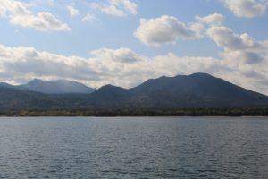 湖上から見た雌阿寒岳(左奥)とフップシ岳(右)